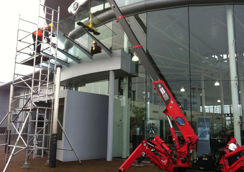 A URW-095 mini spider crane installing canopy glass at a Bentley dealership