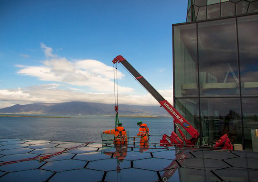 A URW-295 had no problem helping install glass on the floors below in Iceland